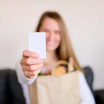 オンラインショッピングのためのクレジットカードを保持している女性