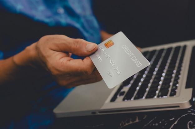 Женщина, держащая кредитную карту онлайн-шоппинг электронной коммерции, оплачивая портативный компьютер дома