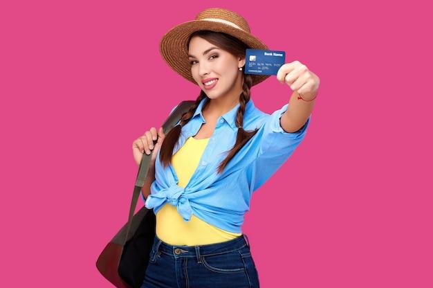 ピンクの分離の背景の上にクレジットカードを保持している女性。スタジオショット。オンラインショッピング、eコマース、インターネットバンキング、お金を使う、人生の概念を楽しむ