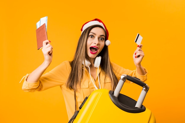 Woman holding credit card and plane tickets posing next to luggage