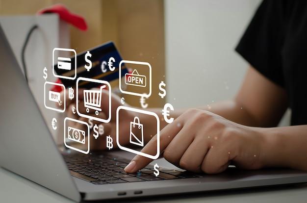 Женщина, держащая кредитную карту с помощью компьютера, чтобы делать покупки в интернете дома