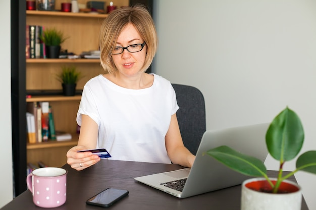 Woman holding a credit card while shopping online on the laptop