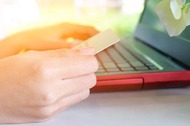Женщина, держащая кредитную карту с ноутбуком в кафе с солнечным лучом света в утро, интернет-магазин