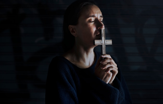 Woman holding cross praying for god religion