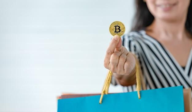 暗号通貨のコインとさまざまな色の買い物袋を手に持っている女性。現代人の実生活で使用する暗号通貨支払いとデジタルマネーの概念。