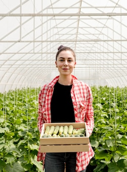 Woman holding cucumbers in greenhouse