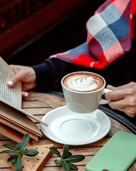 Woman holding a cup of cappuccino and reading a book