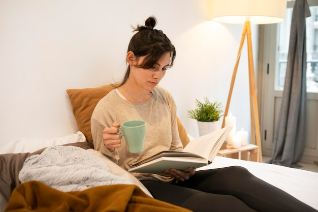 Woman holding a cup of coffee and reading a book