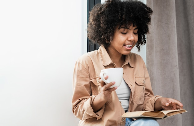 Woman holding a cup of coffee and reading