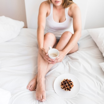 Woman holding cup of coffee with waffles on plate