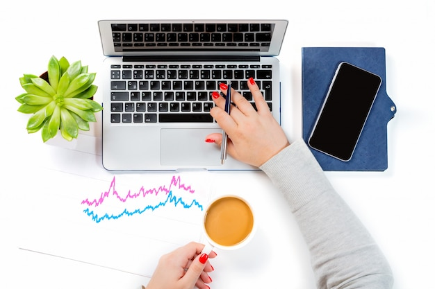 Woman holding cup of coffee and working on modern laptop near mobile phone, plant pot and finance graph chart
