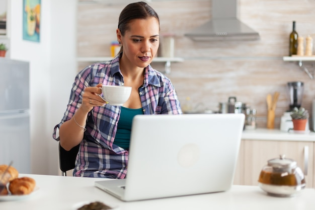 Woman holding cup of hot tea and using laptop in the morning