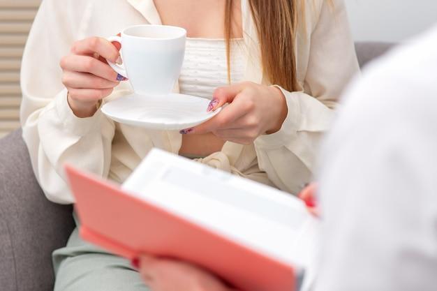 Женщина, держащая чашку кофе во время консультации с врачом во время лечения кофе-брейка