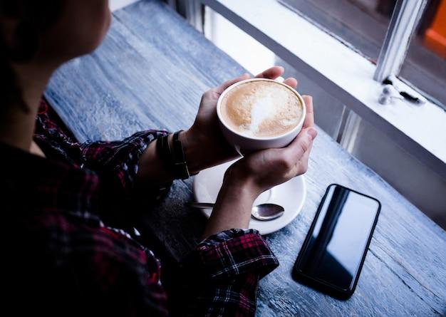 カフェで一杯のコーヒーを保持している女性