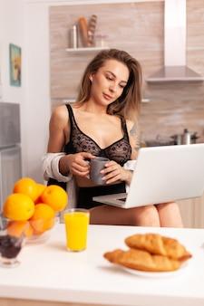 セクシーな下着を着て、キッチンでラップトップを使用してコーヒーのカップを保持している女性。魅惑的な下着の笑顔に身を包んだキッチンに座ってpcに入れ墨を入力して魅力的なブロンドの女性