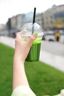 通りで緑のスムージーのカップを保持している女性