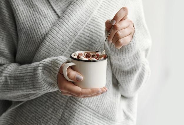 マシュマロ、クローズアップとおいしいココアのカップを保持している女性