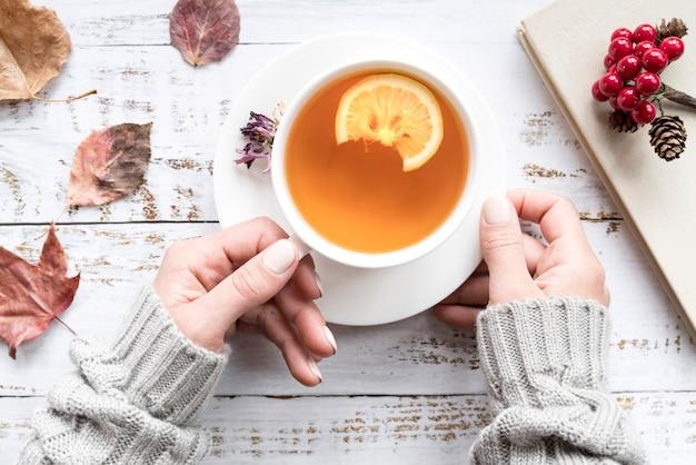 葉の間でお茶のカップを保持している女性