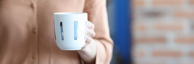 Женщина, держащая чашку чая в руке в офисе крупным планом