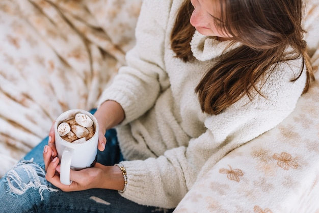 Woman holding cup with marshmallows on sofa