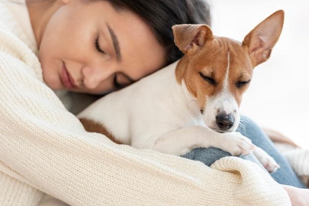 Женщина держит симпатичную но сонную собаку
