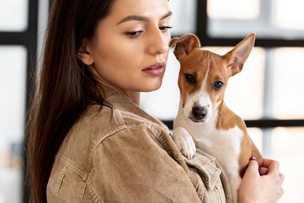 Donna che tiene cane sveglio mentre posando
