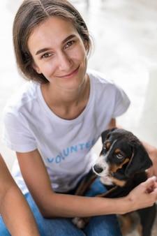 Donna che mantiene carino cane da salvataggio in adozione