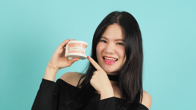 Woman holding dental teeth model or orthodontic model. oral care concept.