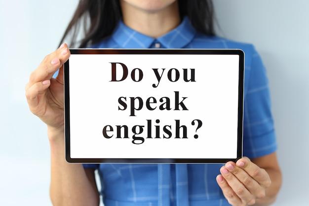 碑文とデジタルタブレットを保持している女性あなたは外国語を学ぶ英語のクローズアップを話しますか