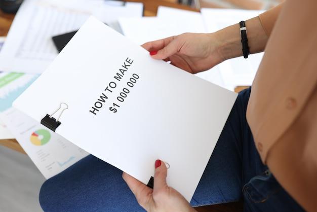 Женщина, держащая в руках документы с названием, как сделать крупным планом