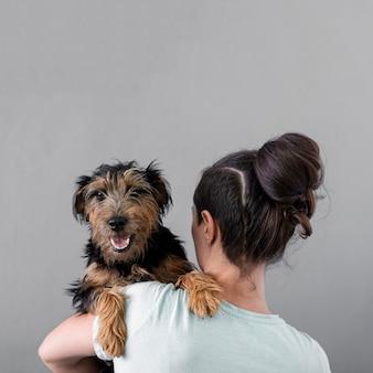 Женщина держит собаку с копией пространства