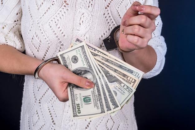 Woman holding dollar bills in handcuffs