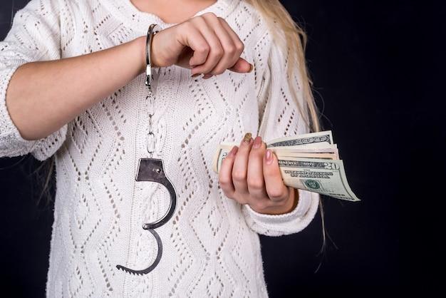 手錠でドル札を保持している女性
