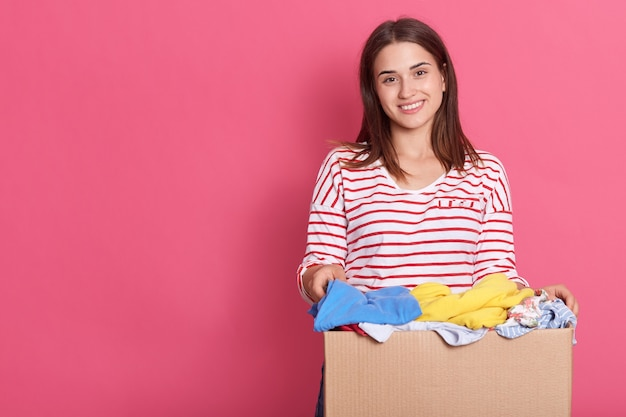 Woman holding donate box full of clothes