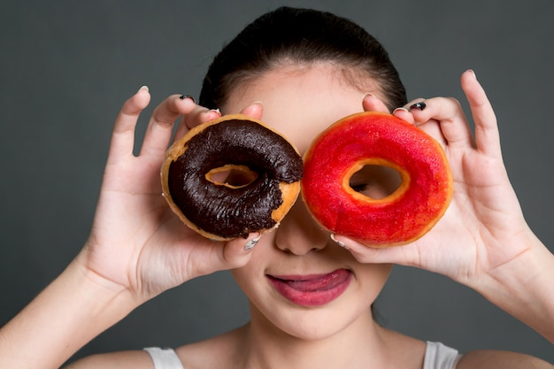Woman holding donut on eye on gray background