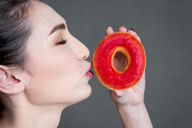Woman holding donut on gray background