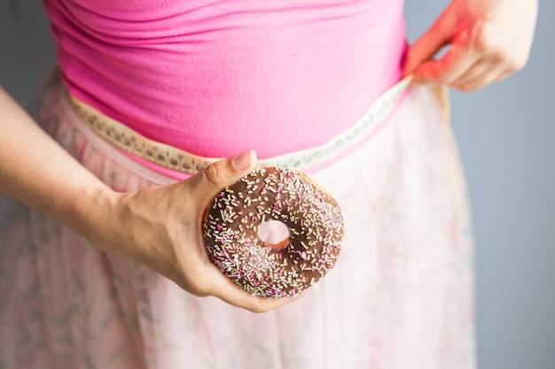 여자는 도넛을 손에 들고 측정 테이프로 체지방을 확인합니다.