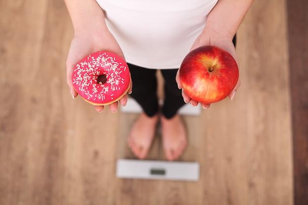 Женщина, держащая пончик и яблоко