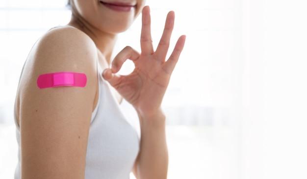 백신 접종 후 셔츠 소매를 누르고 붕대로 팔을 보여주는 여성, 코비드-19 또는 코로나 바이러스 예방 접종을 위해 마스크를 쓴 환자, 건강 및 백신 개념