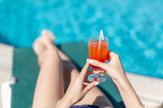 Woman holding drink laying on lounge