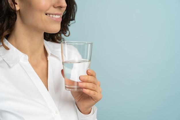 彼女の手で飲料水ガラスを保持している女性は、スタジオの青い背景で隔離。健康的な生活様式