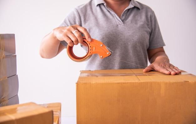 Женщина, держащая клейкой лентой для упаковки продуктов для подготовки поставок