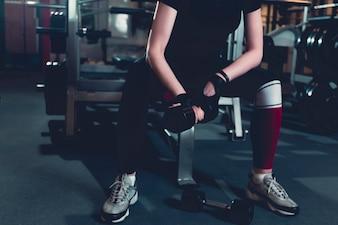 Woman holding dumbbell in fitness center