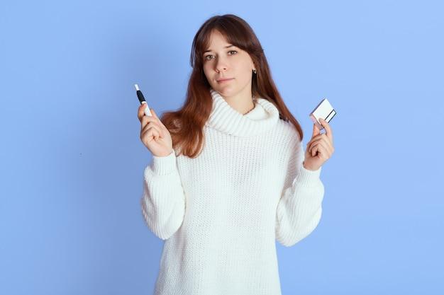 Женщина, держащая электронную сигарету и палку на синем