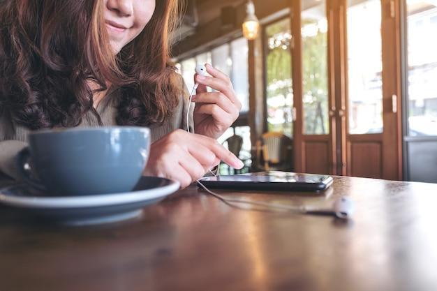 カフェで携帯電話で音楽を聴きながらイヤホンを持っている女性