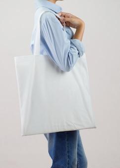 Женщина, держащая эко ткань изолят на сером фоне