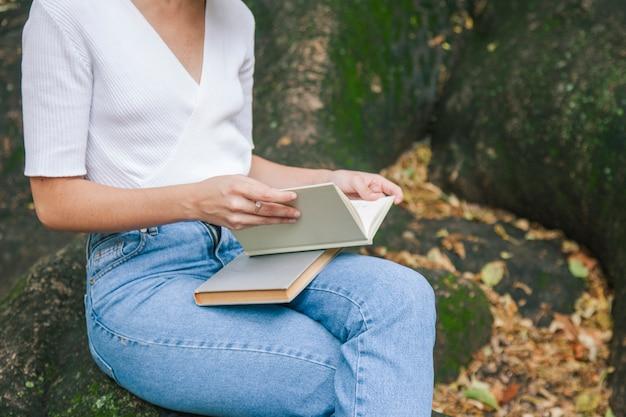 Женщина, держащая учебники в парке