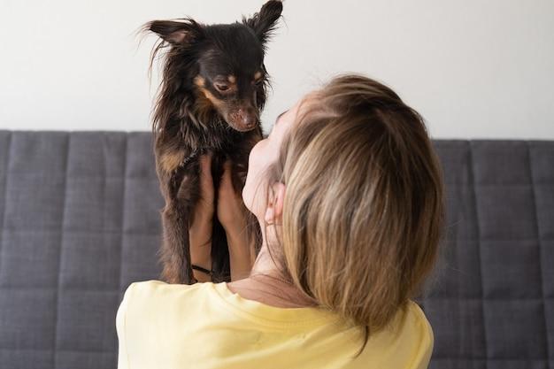 Женщина, держащая объятия смешной коричневый русский той терьер. концепция ухода за домашними животными. любовь и дружба