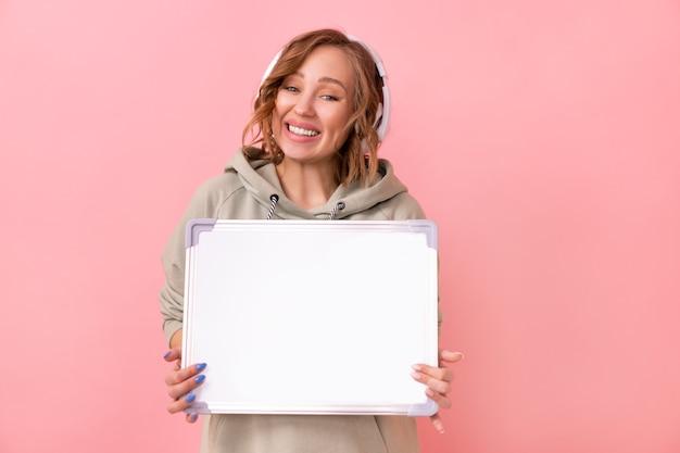 ピンクの背景の上に空の空白のボードを保持している女性幸せな白人女性30歳の服を着たヘッドフォン特大パーカー
