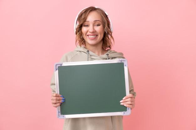 ピンクの背景の上に空の黒板を保持している女性